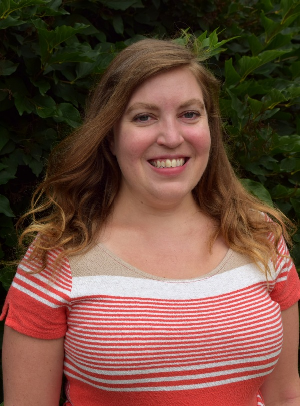 Alison Moffat, a white woman with shoulder length light brown hair, is standing in front of a  leafy background. She is wearing a brightly colored pink and white top.