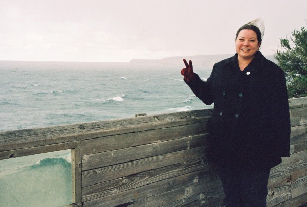Leslie Mehle, a white woman with dark hair, is standing near a lake and showing the peace sign with her left hand.