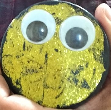 This image shows a glittery, golden hockey puck with googly eyes. It is a placeholder for a picture of a person.
