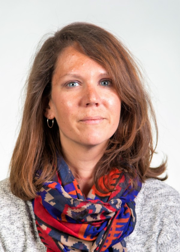 Headshot of Lisa Wheeler, a white woman with shoulder length brown hair. She is wearing a colorful scarf and a white top.