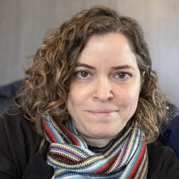 Erin Callahan, a white woman with brown curly hair, is looking at the camera in this headshot. She is wearing a colorful scarf and black shirt.