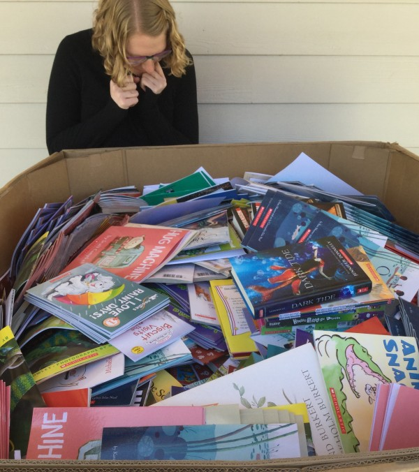 Hannah Buckland, a white woman with blond hair, is standin near a very large cardboard box full of colorful books.